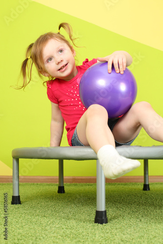 Funny little girl with pigtails sitting on a trampoline