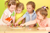 Two boys and two girls doing together wooden puzzle - 58516339