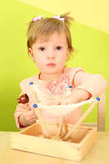 A little girl in a pink blouse playing with wooden toy