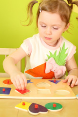 Little girl with pigtails puts wooden geometric shapes