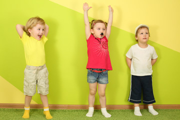 Two boys and a girl standing at the bright green wall
