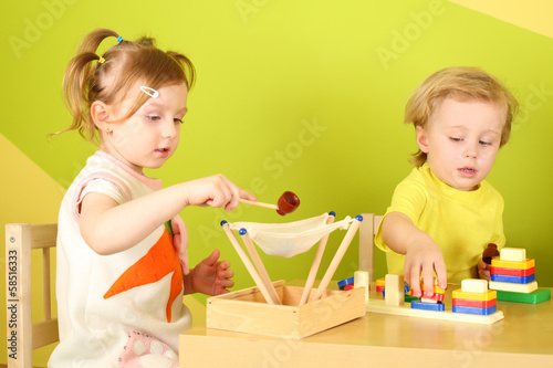 Little boy and girl sitting at the table and play with toys