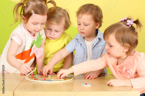 Two boys and two girls doing together wooden puzzle