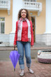 A young woman in a red jacket and rubber boots