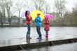 Mother and two children standing in the rain on a pier