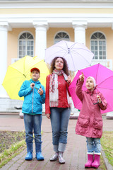 Mother with two children stand with colorful umbrellas