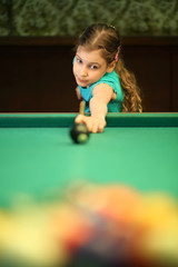 The girl starts the game of billiards