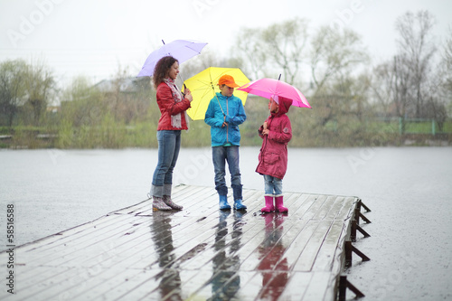 Mother and two children standing in rain on a pier