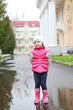 Cute girl in bright clothes standing in a puddle