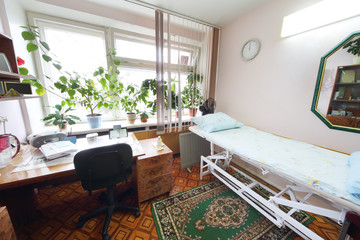 Interior of a light doctors consulting room with a bed
