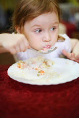 Little girl with a surprised expression on her face eating spagh