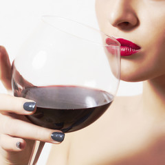 Beautiful woman drinking red wine.wineglass.red lips