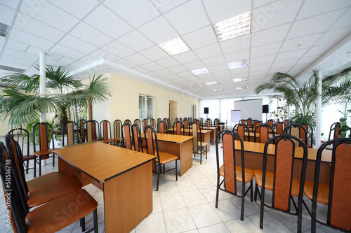 Interior of conference hall with row of chairs and tables