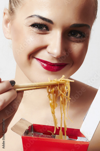 happy beautiful woman eating chinese food. red lips.smile
