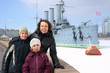 A mother with two children against the cruiser Aurora