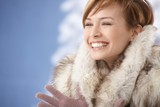 Happy young woman wearing fur coat