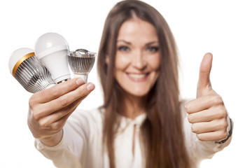 girl holding a LED bulbs in one hand and  showing thumbs up
