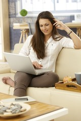 Happy woman using laptop at home on sofa