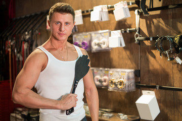 A muscular man in a vest holding a whip in the wooden room