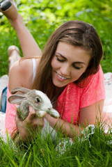 Young happy woman embracing little rabbit outdoors