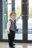 Boy in business clothes opens door to business center