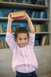 Mulatto boy in shirt holding a book over his head