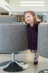 A little girl in adress standing between the seats