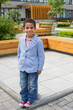 Mulatto boy in a striped jacket in park with fountains
