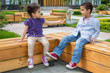 Little girl treats the boy cookies on bench in park