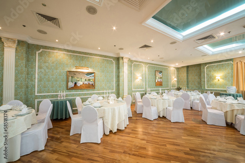 hall with tables in restaurant decorated for wedding celebration - 58518374