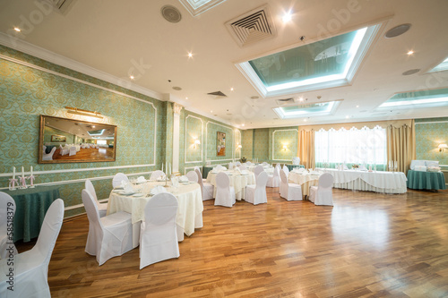 Beautiful room with tables in restaurant decorated for wedding