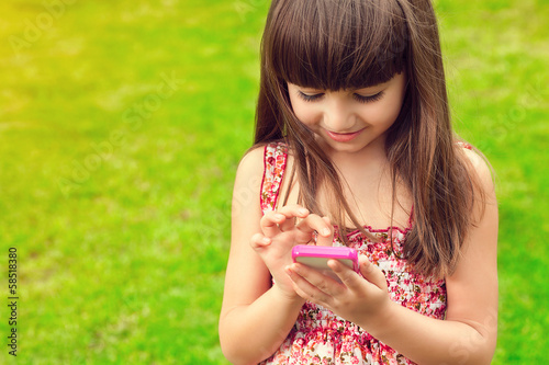 beautiful girl holding a phone on a background of green grass
