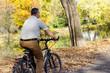 Man rides his bike through the park in autumn