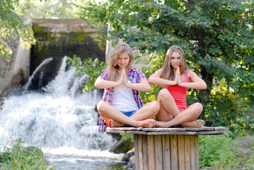 Two teen girls sitting in yoga position