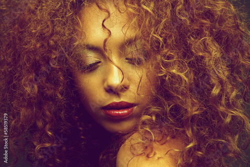Young female fashion model with curly hair covering face