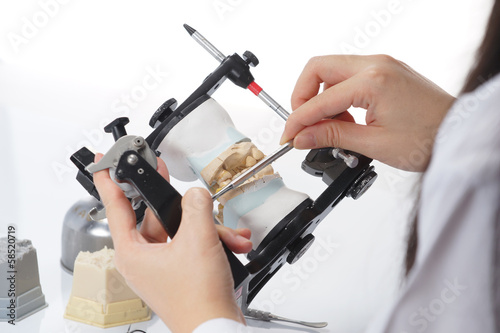 Dental technician working with articulator in dental laboratory