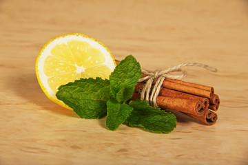 Cinnamon sticks, segment of a lemon and mint