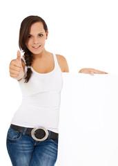 Attraktive junge Frau neben weißem Schild zeigt Daumen hoch