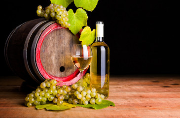 White wine and grapes in front of old barrel