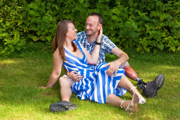 Loving couple sitting on the grass.