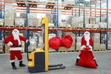 two santa clauses workers at work in large storehouse