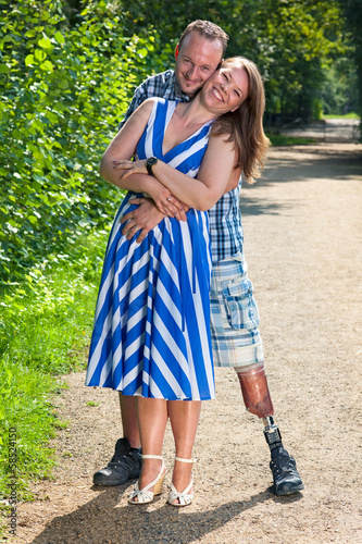 Disabled man and attractive woman in loving hug.