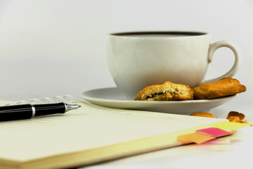 cup of coffee,cookies,notebook and pen isolated on white backgro