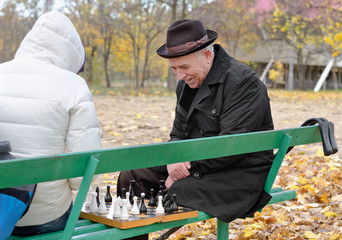 Elderly man enjoying a game of chess in the park