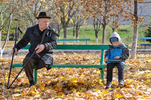 Elderly handicapped man watching a young boy