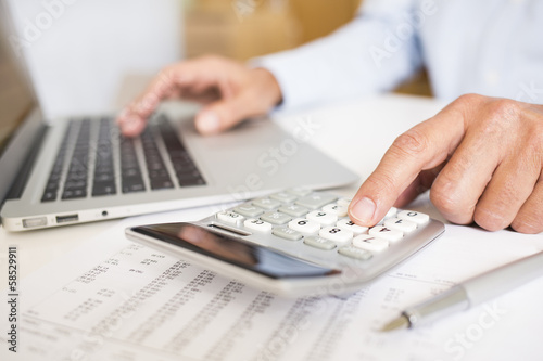 Man doing his accounting, financial adviser working - 58529911