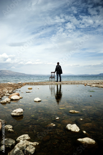 Man standing next to a chair admires the view on the seaside