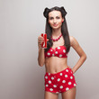 Drinking soda model in vintage shorts and bra