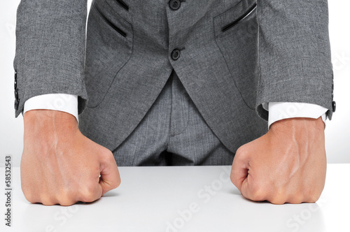 man in suit withs his fists on the desk