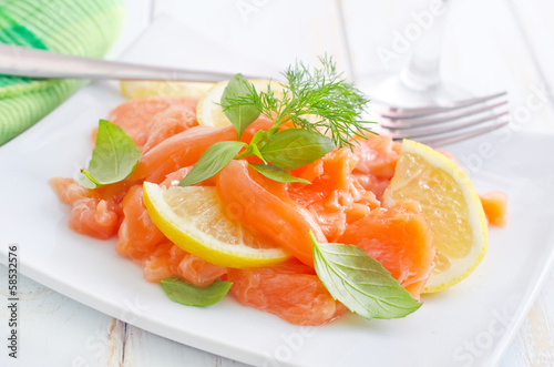 fresh salmon with lemon on the white plate